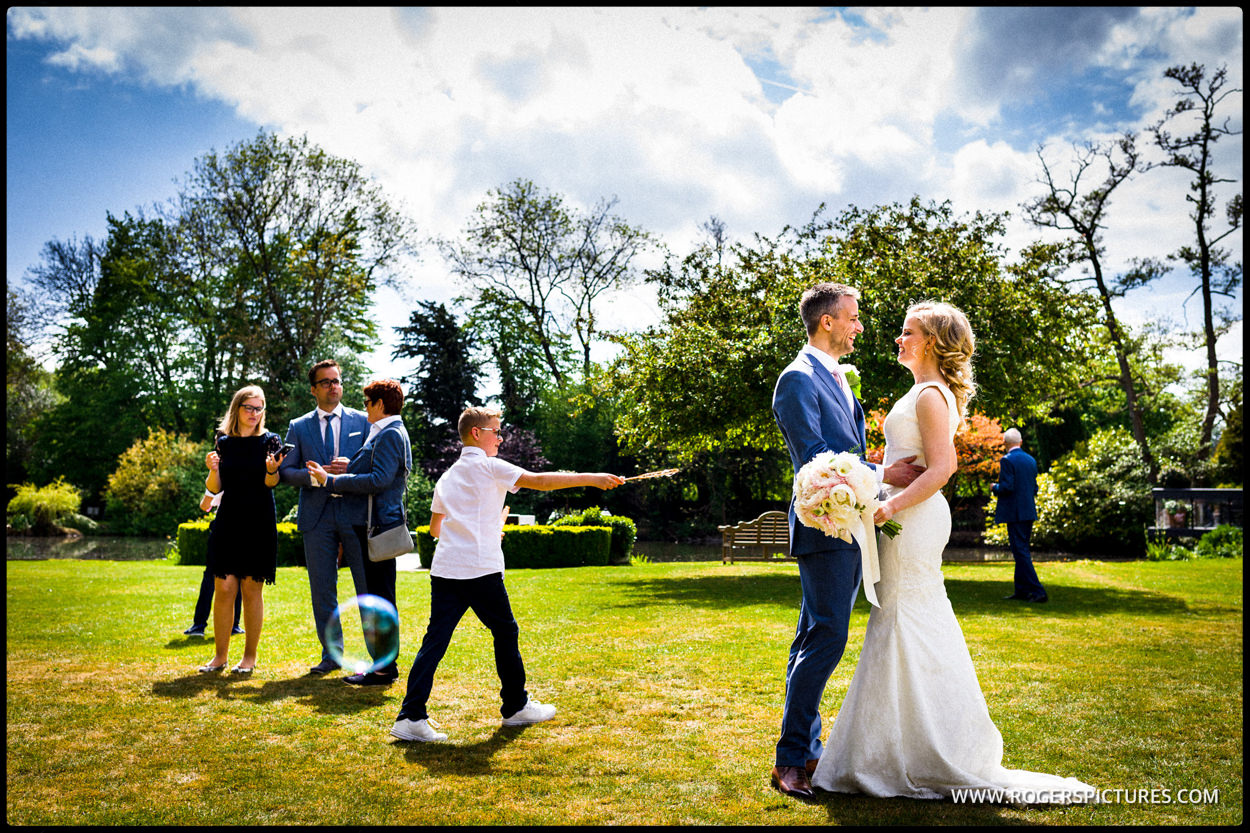 Bride and groom embrace in hotel gardens