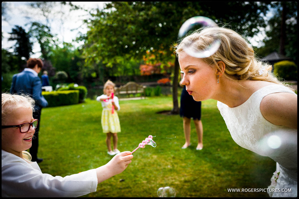 Photo of bride blowing bubbles