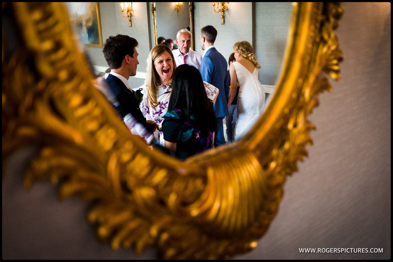 Reflection in oval mirror of wedding guests at a meal