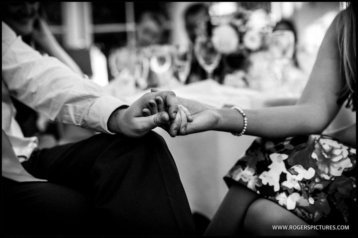 Guests hold hands during the after dinner wedding speeches