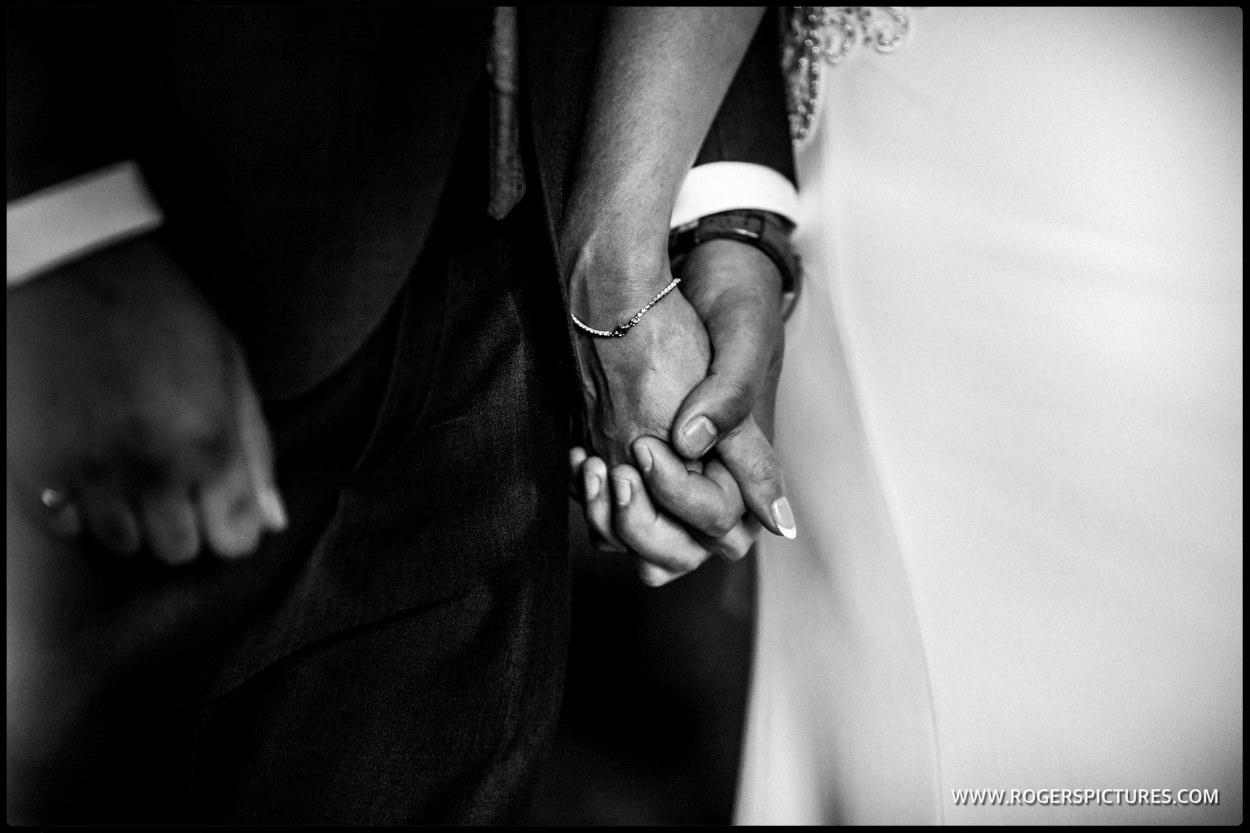 Monochrome photo sharing bridegroom holding hands