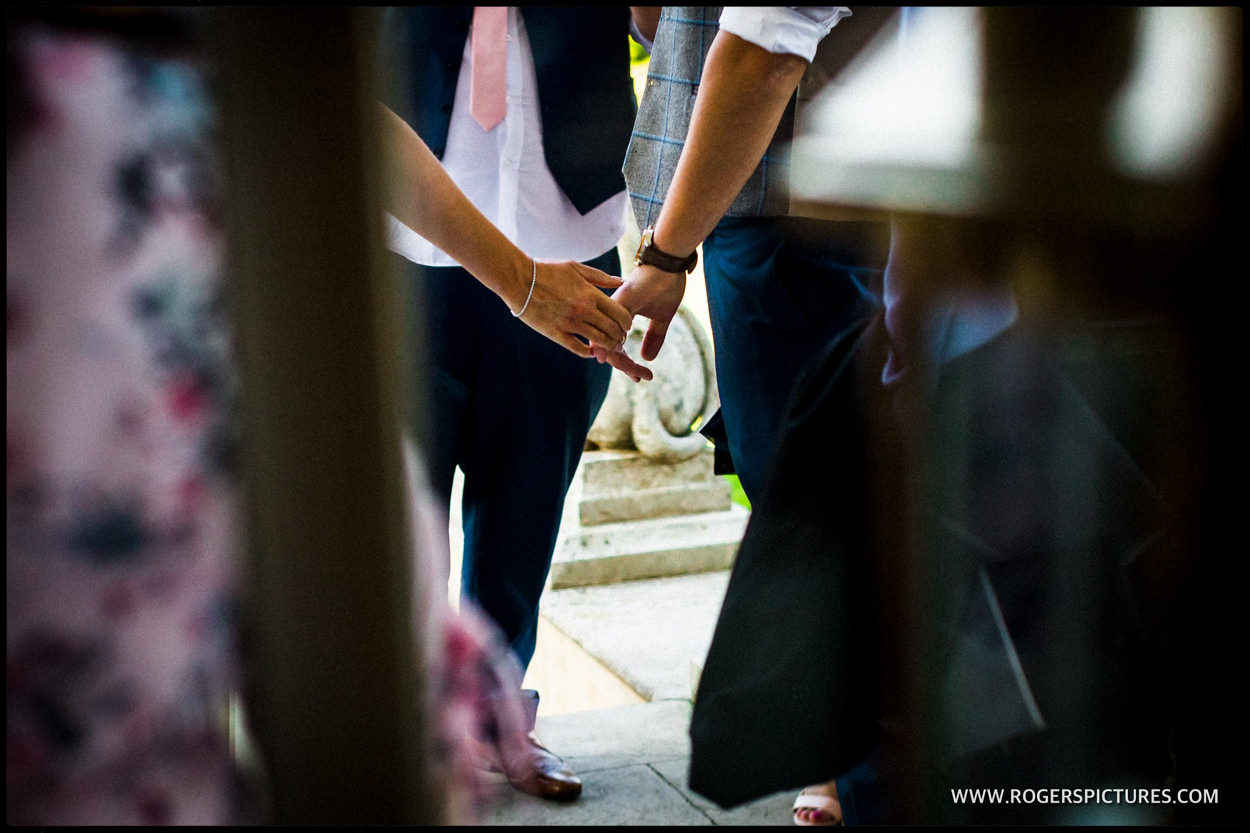 Bride and groom holding hands at Buxted Park