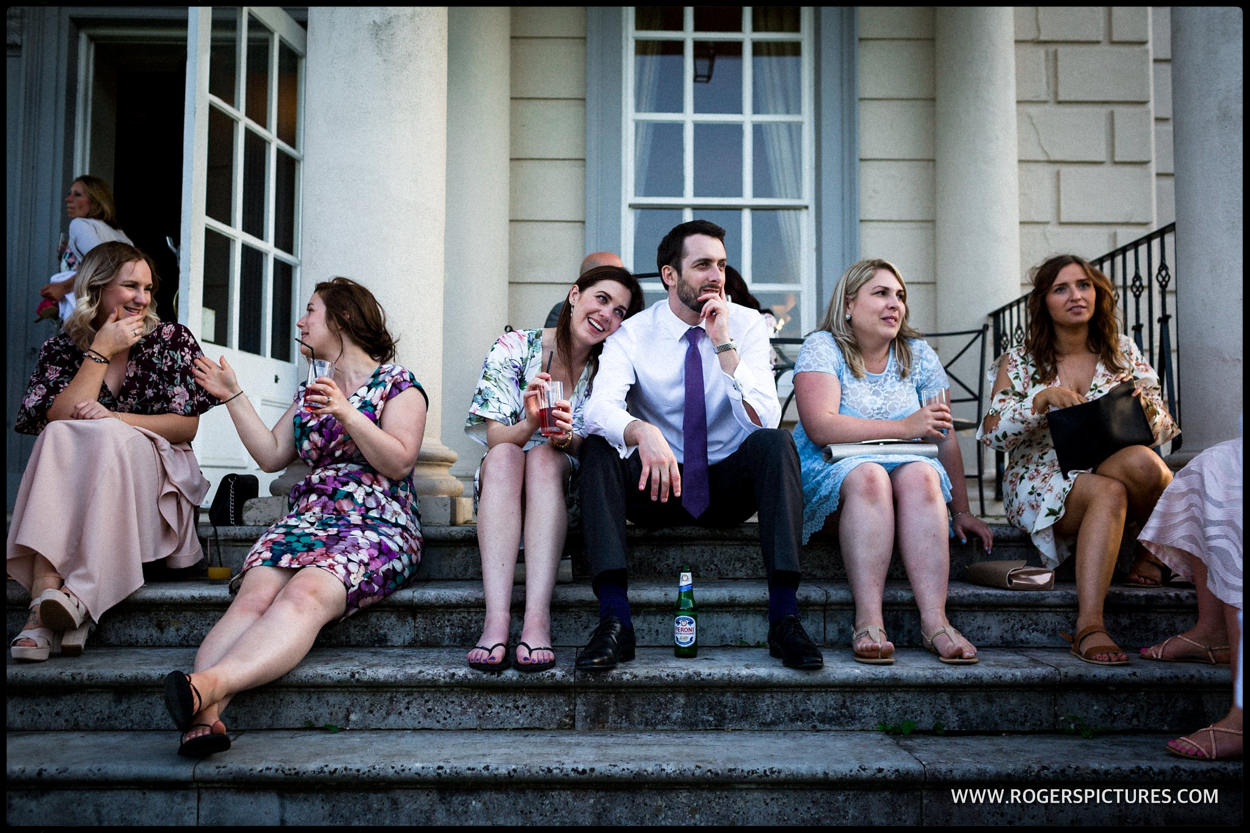Friends sitting on steps chat after wedding ceremony