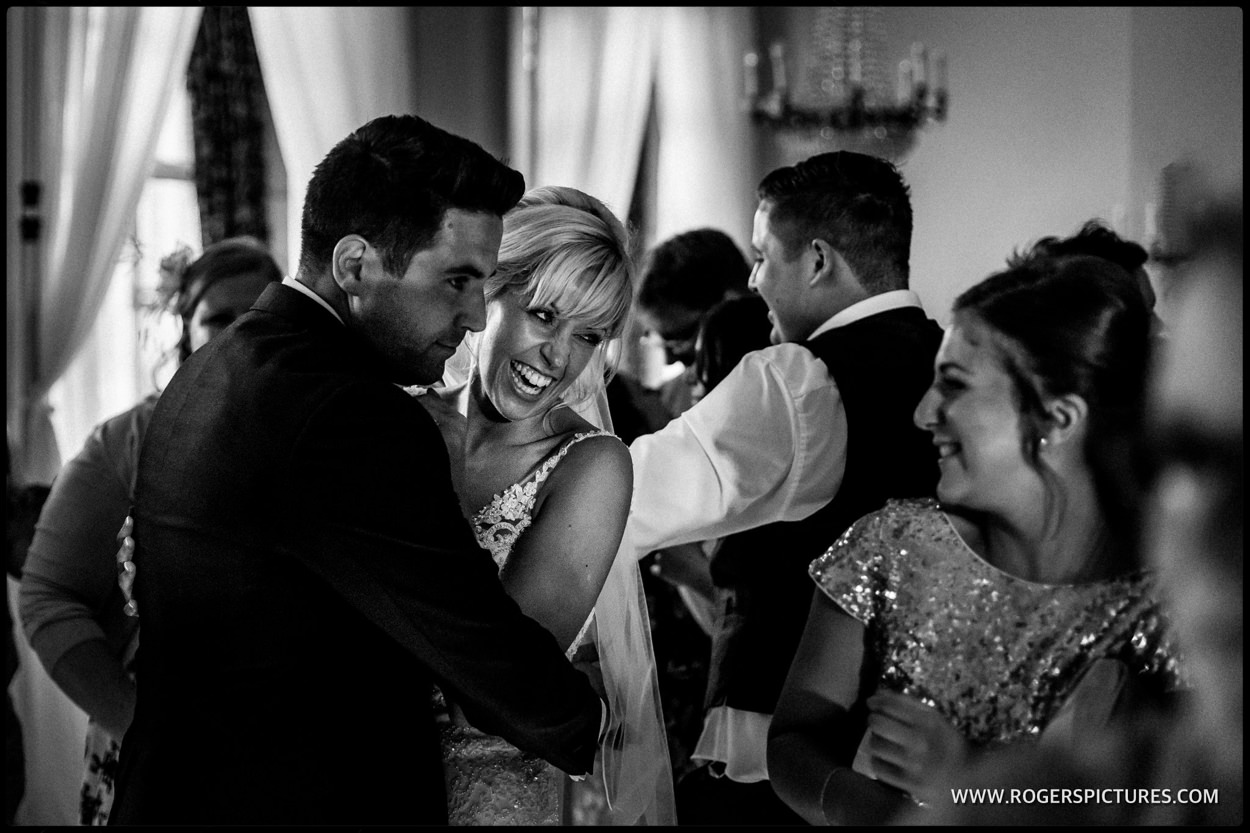 Smiling couple dancing with wedding guests