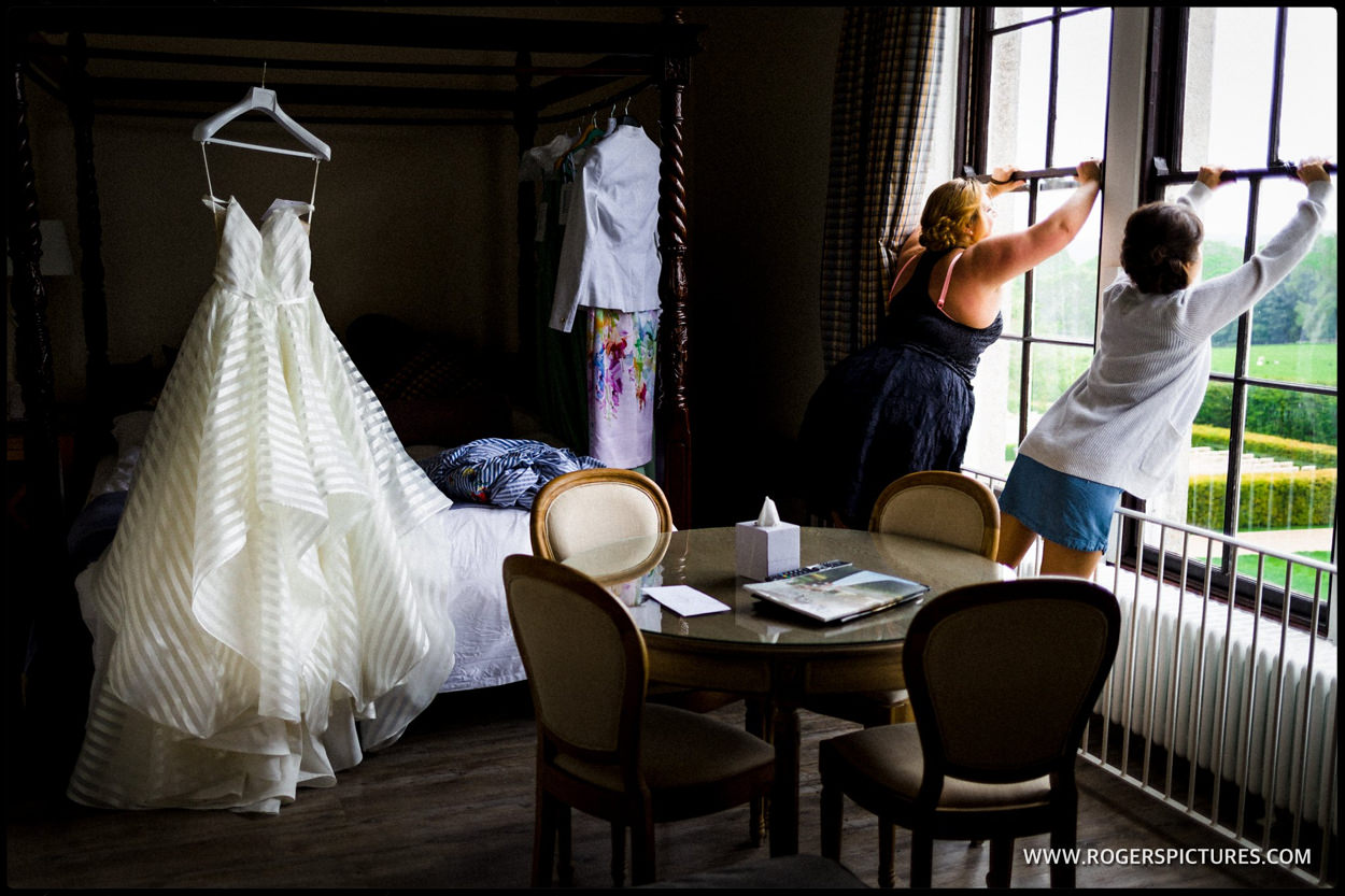 Bridesmaid is open the windows as a wedding dress hangs
