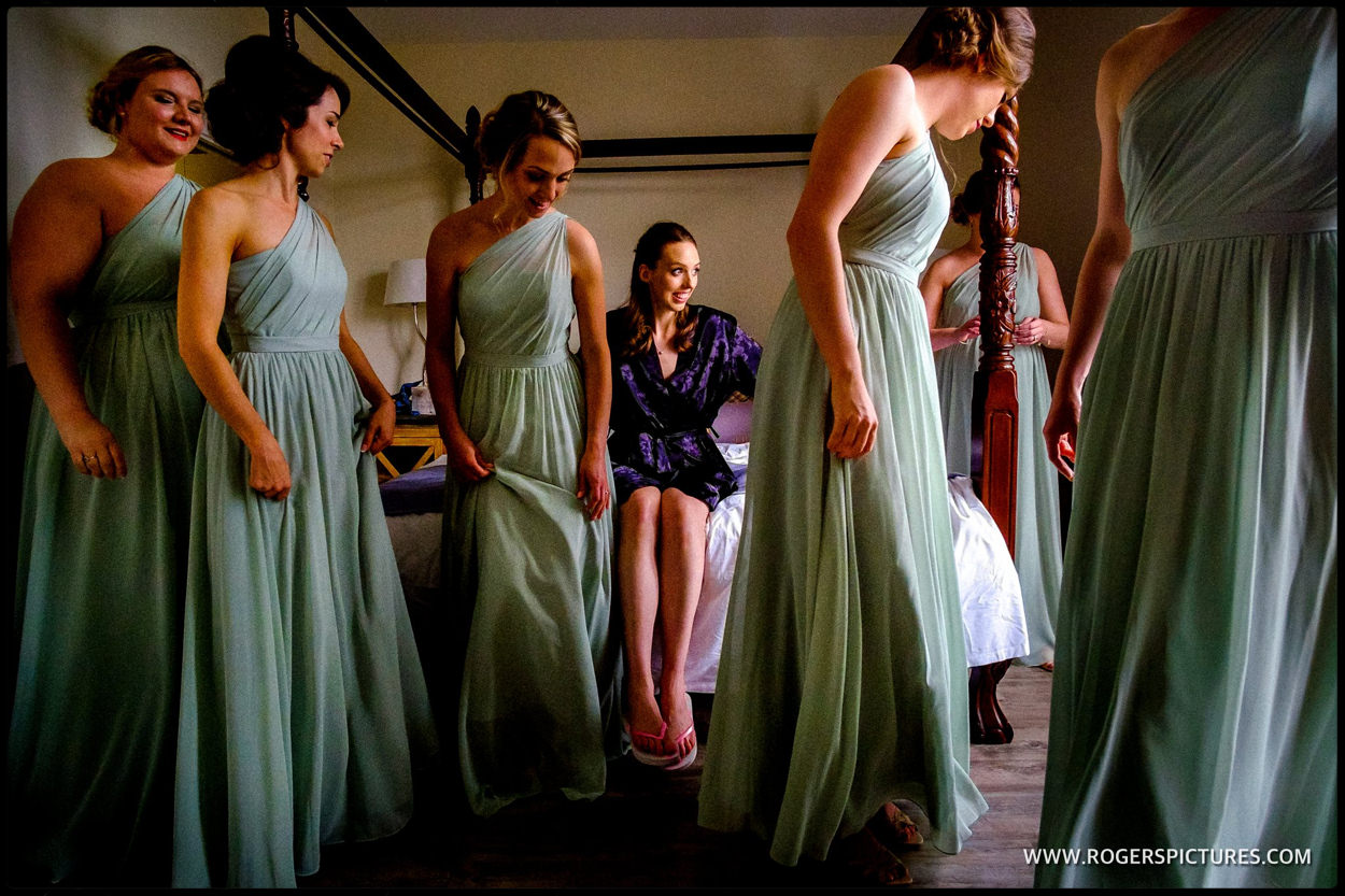 Bride in dressing gown sitting on fourposter bed surrounded by bridesmaids in Emerald addresses