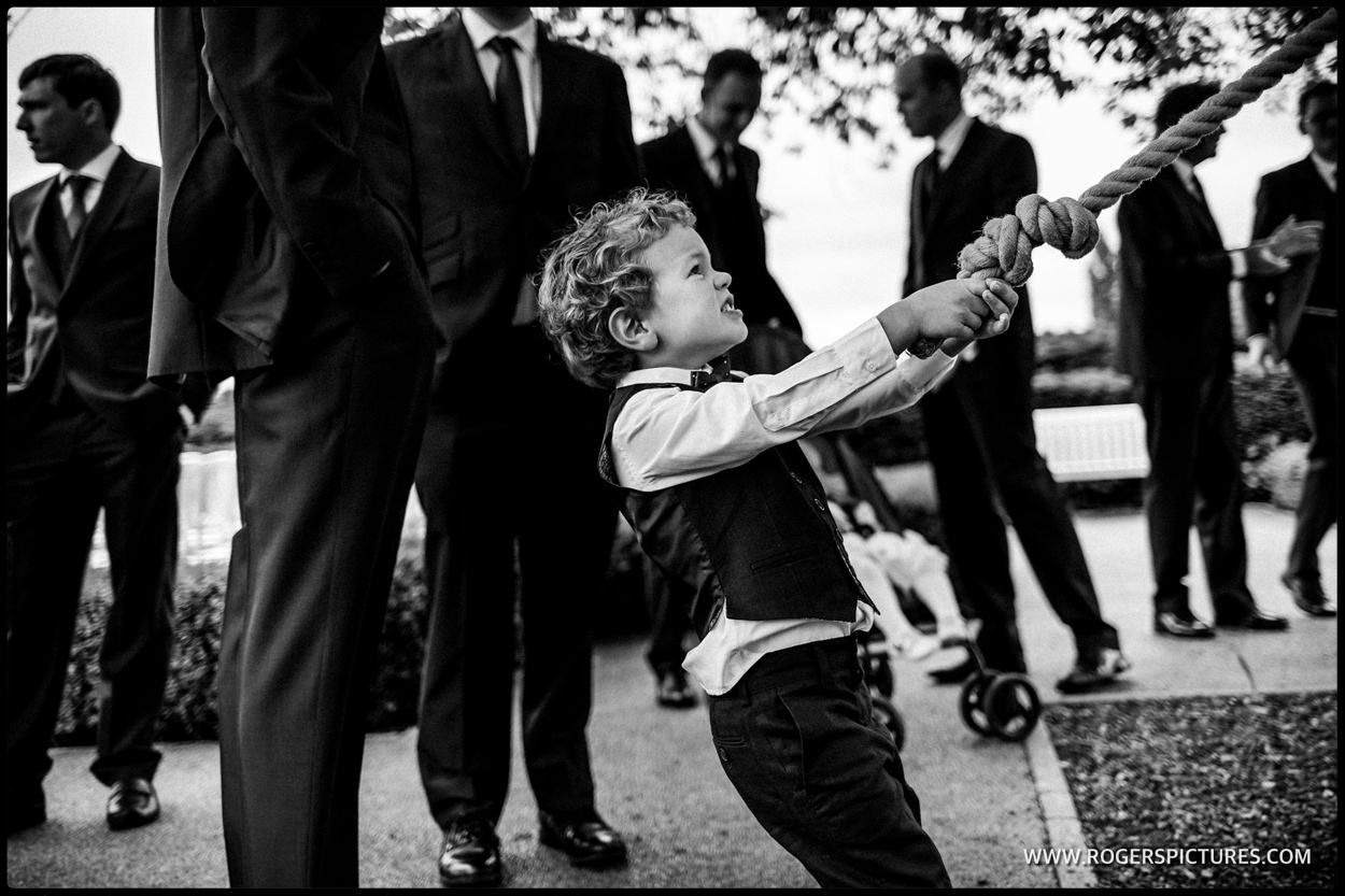A young boy on the rope swing at a wedding