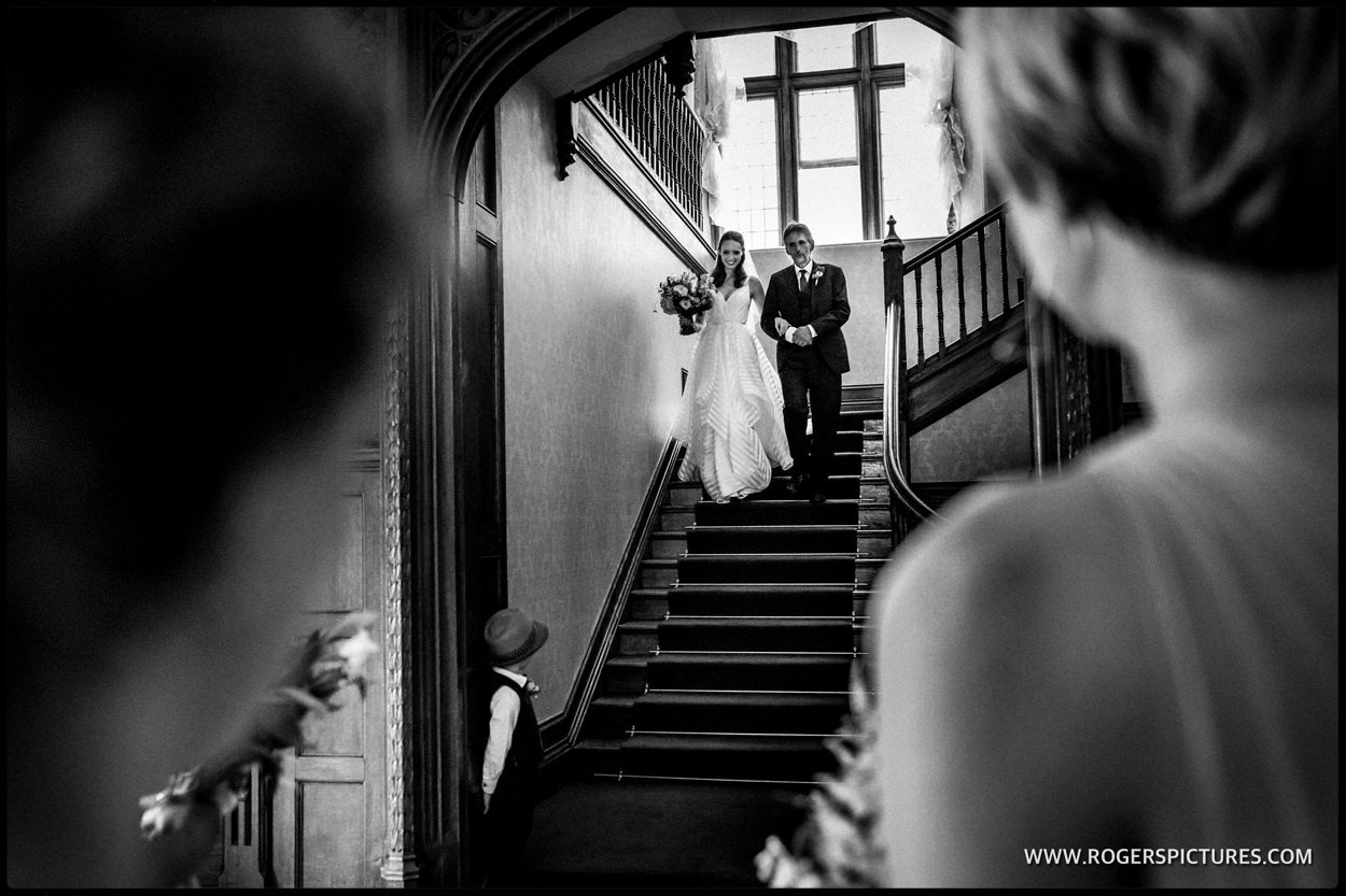 Bridesmaids watch dad and his daughter walking towards the wedding ceremony at Foyle Park