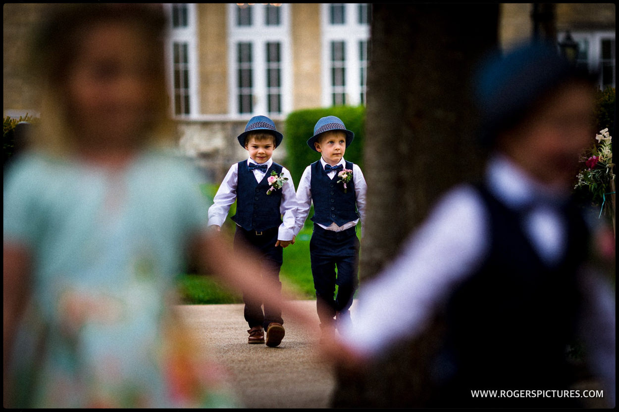 Pageboys walk towards an outdoor wedding ceremony