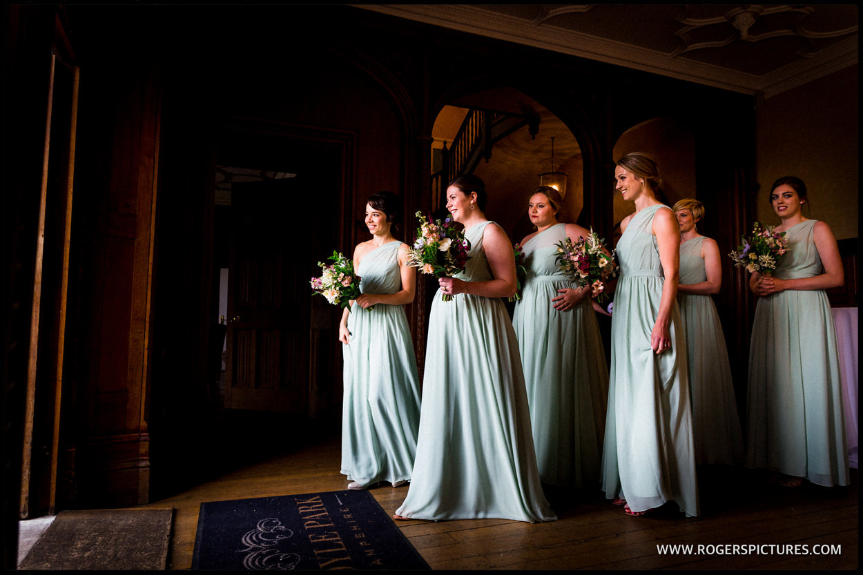 Bridesmaids in Emerald dresses lined up before walking down the aisle at a wedding