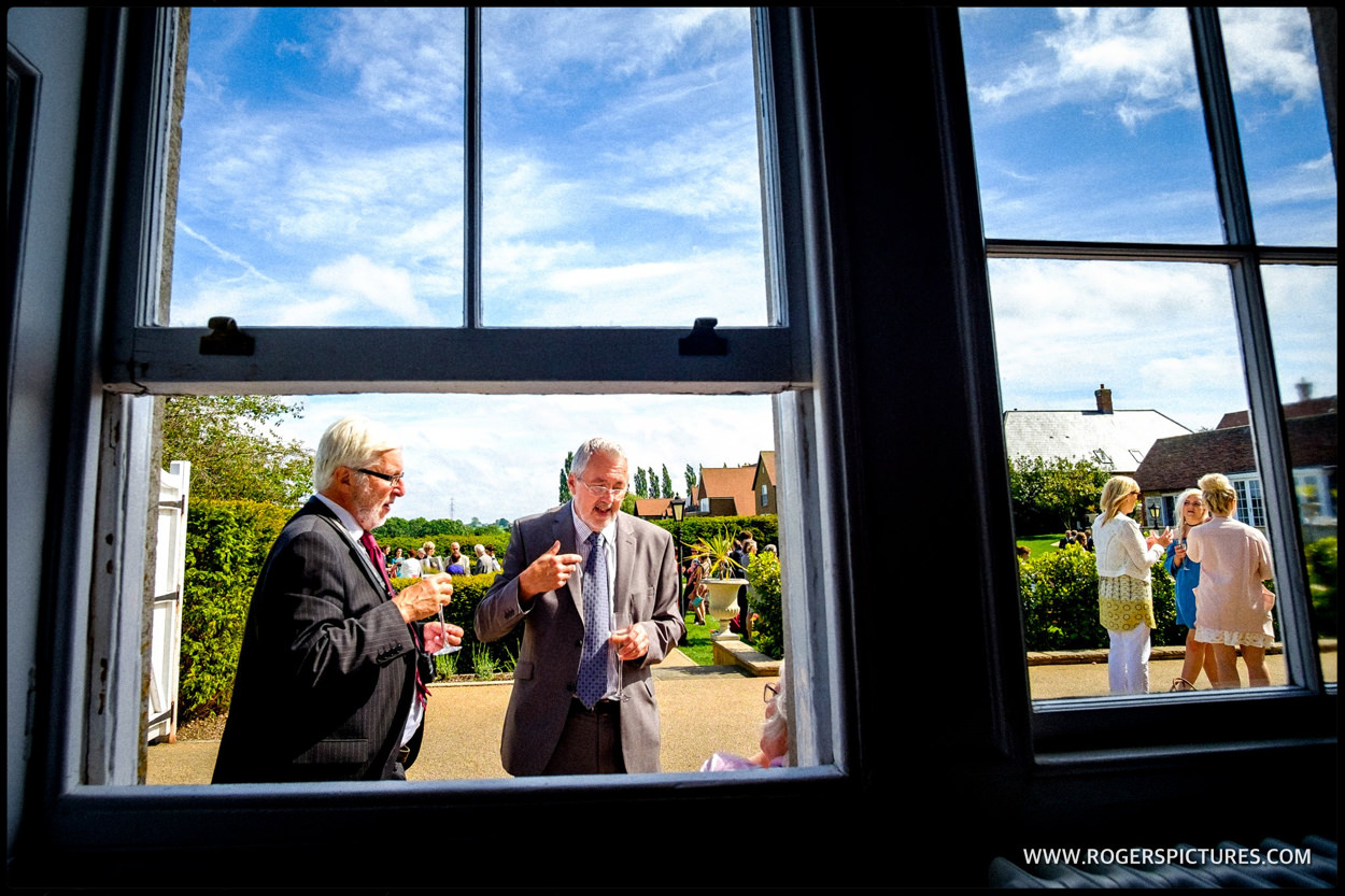 Wedding guests framed in the window during a summer wedding