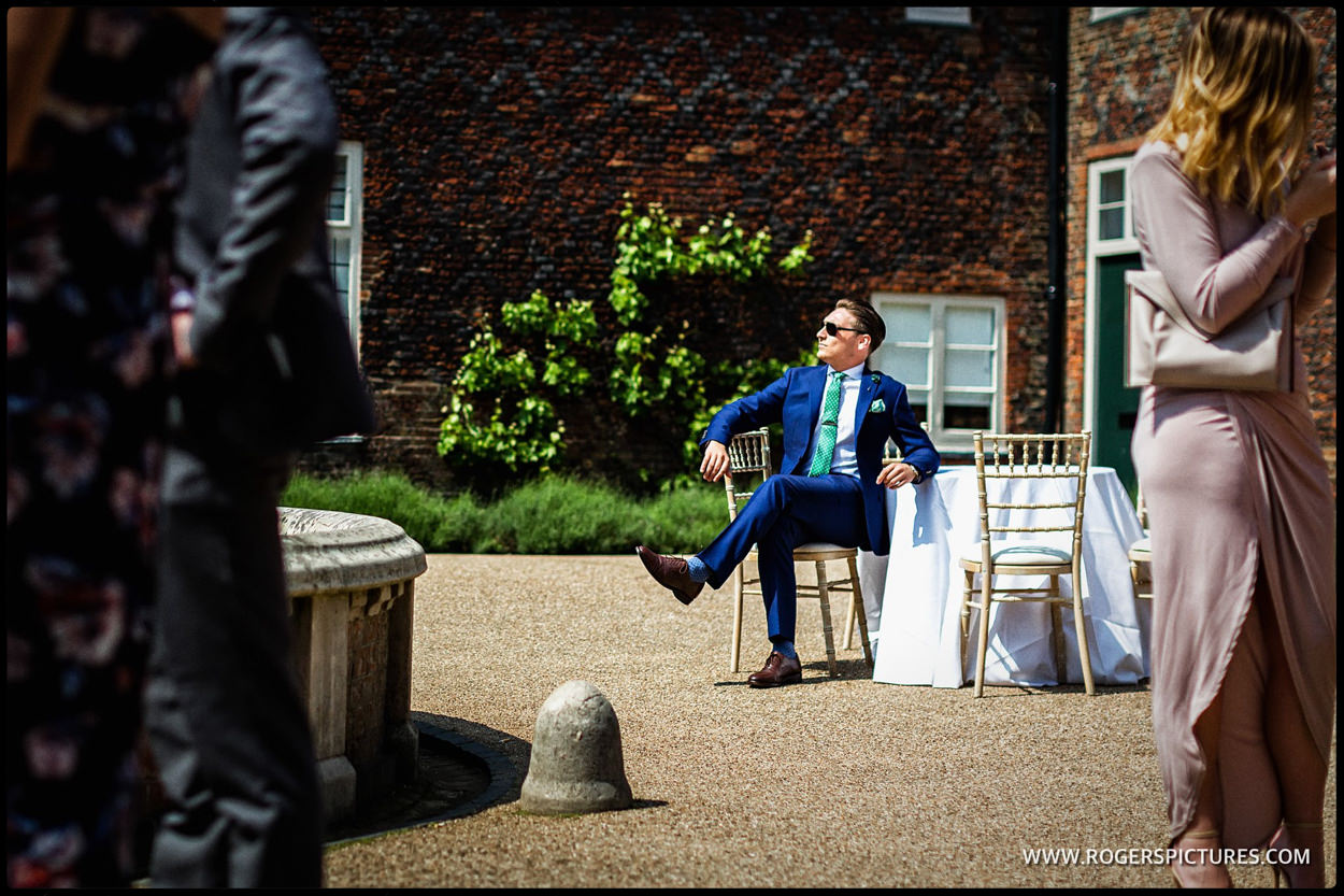 Wedding guest in A blue suit enjoys the sun in the courtyard