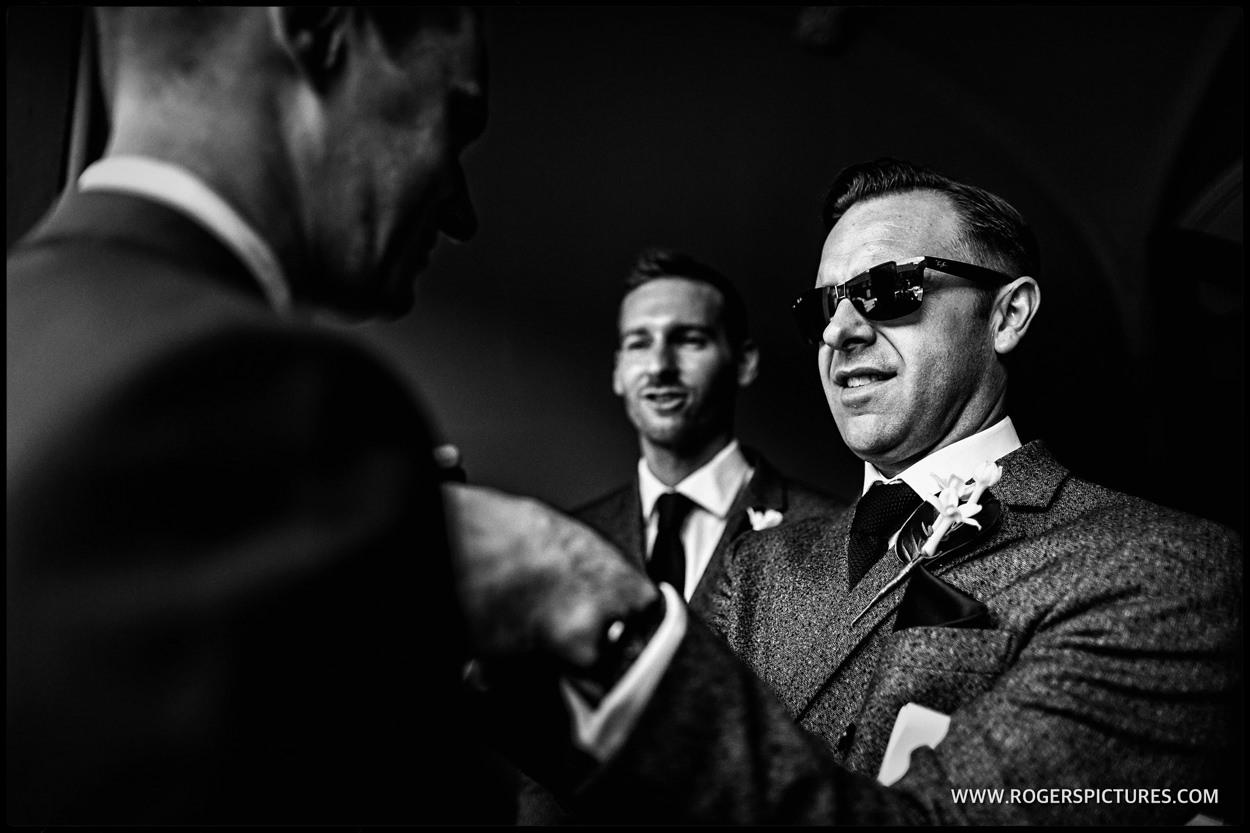 Man in sunglasses adjusts buttonhole