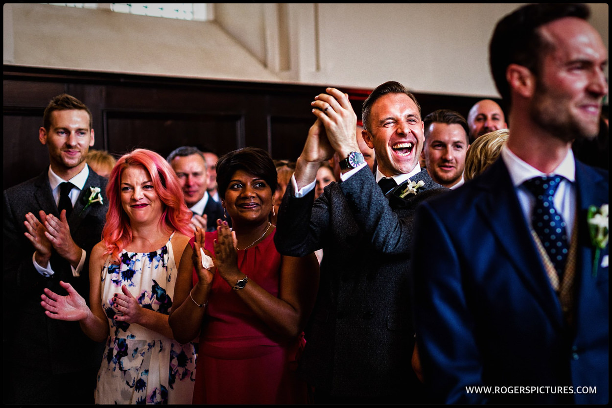 Laughing guests applaud after same-sex wedding ceremony