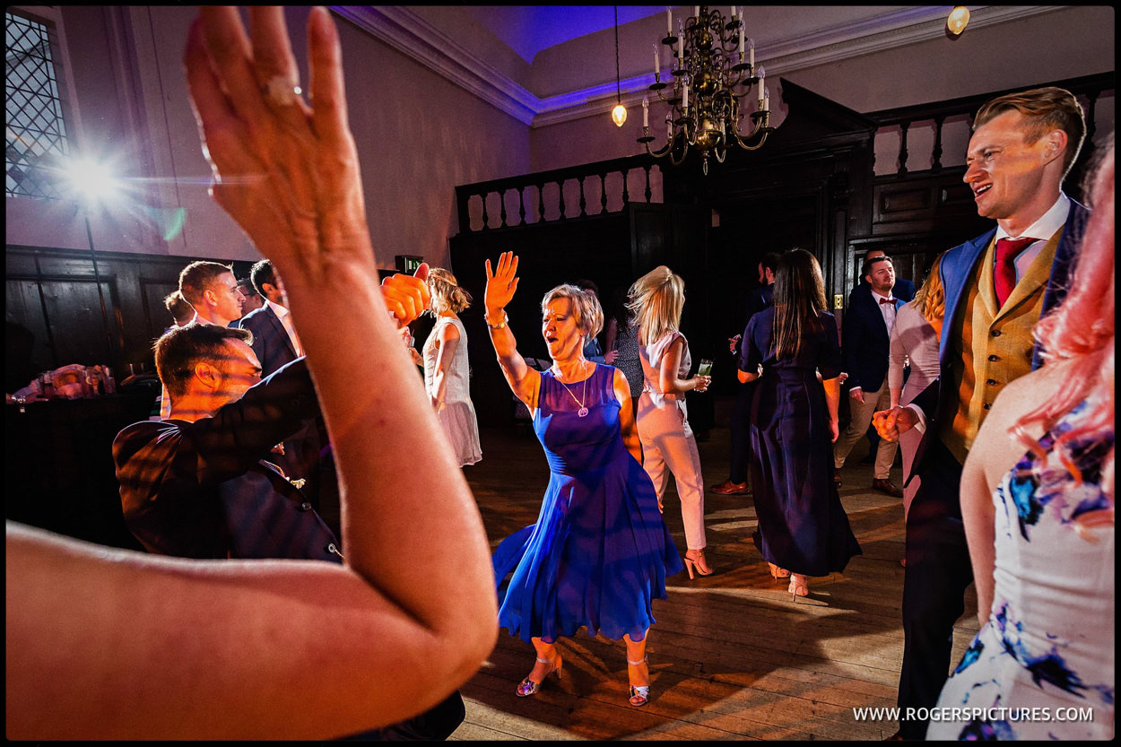 Mother of the Groom in blue dress dancing at a wedding