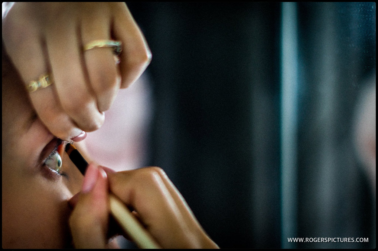 Close-up of pride applying eye make up