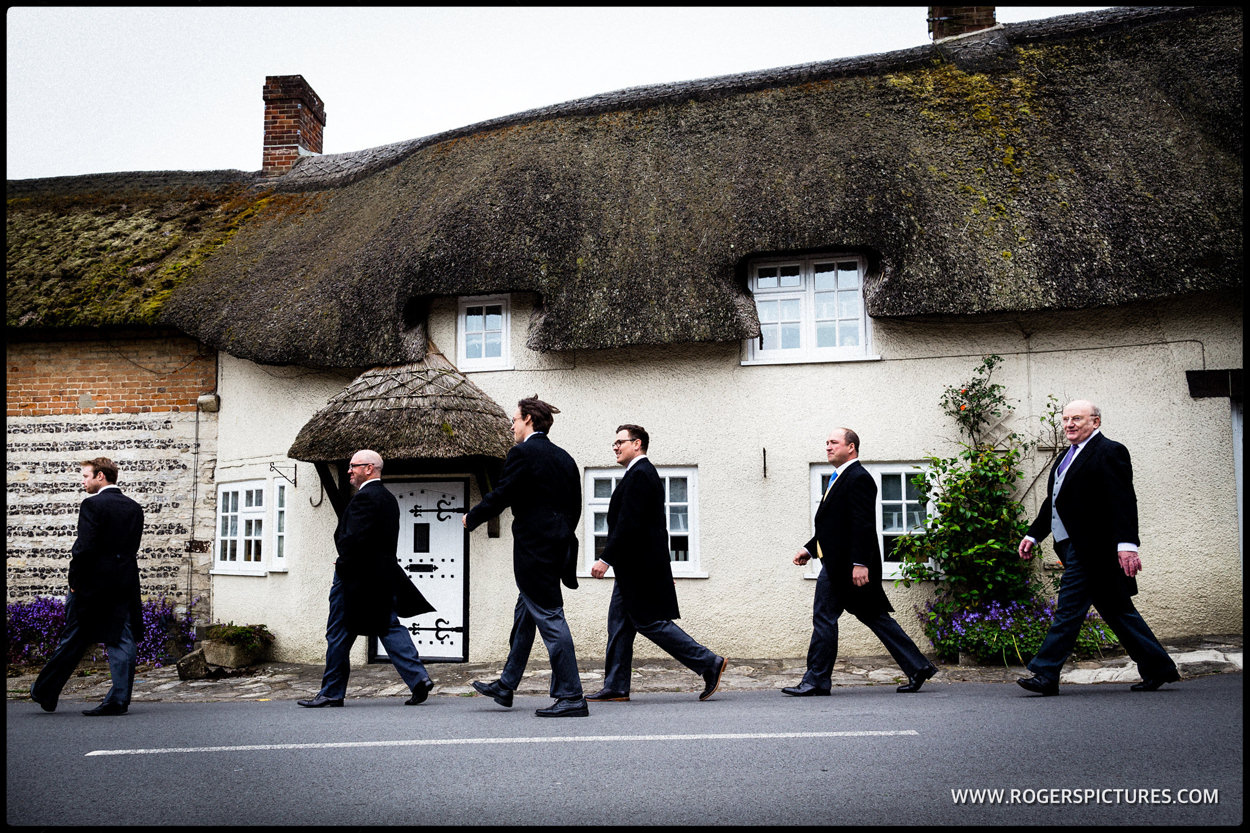 Groom and groomsmen walk past a thatched cottage in Dorset before his wedding