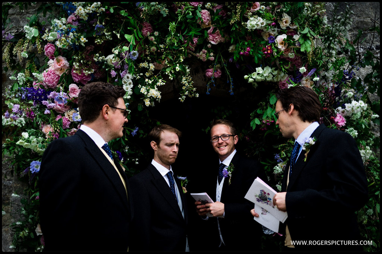 Groomsmen beneath jay Archer flower arch in Dorset
