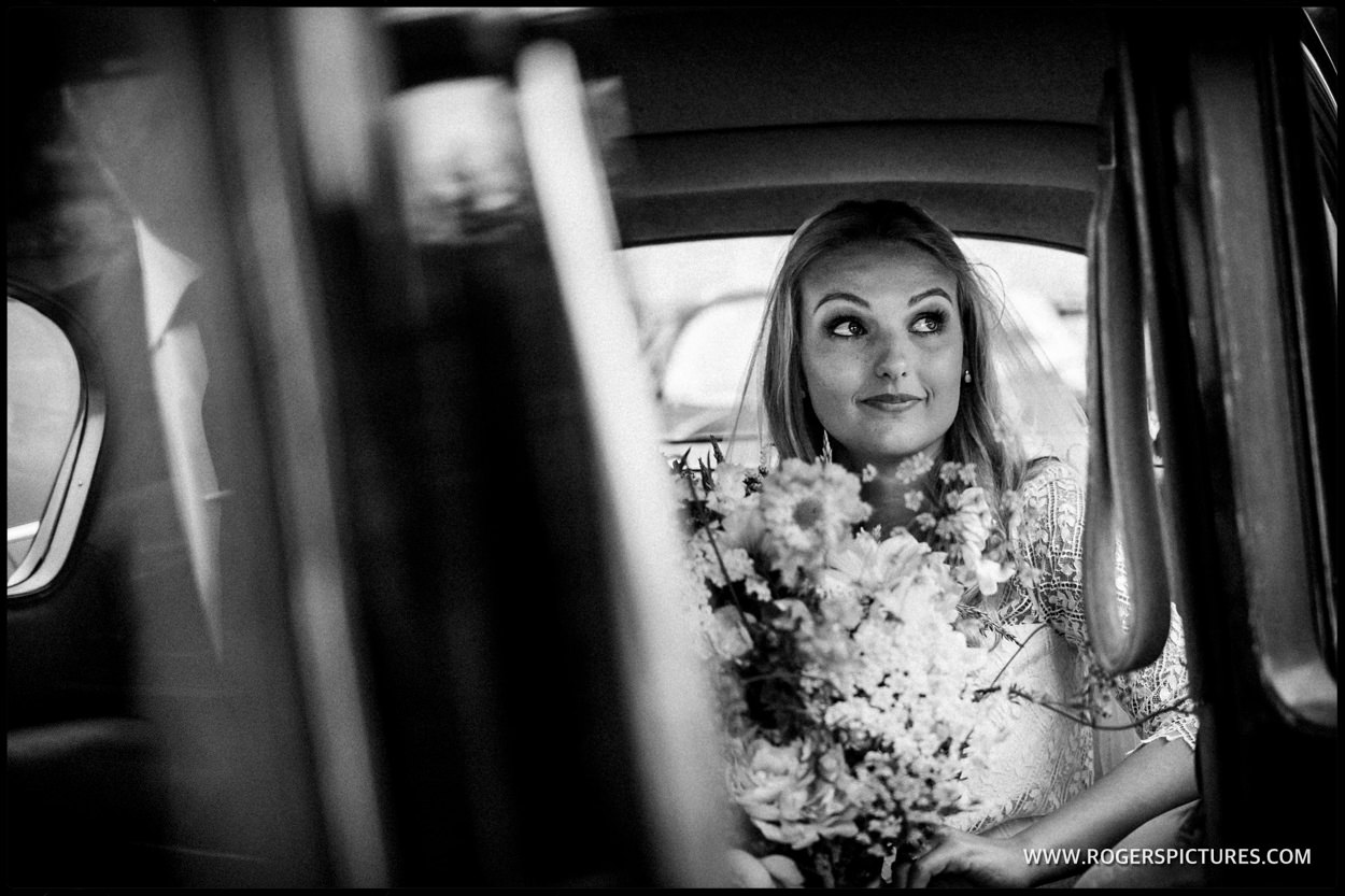 Black and white photo of a bride arriving for her wedding