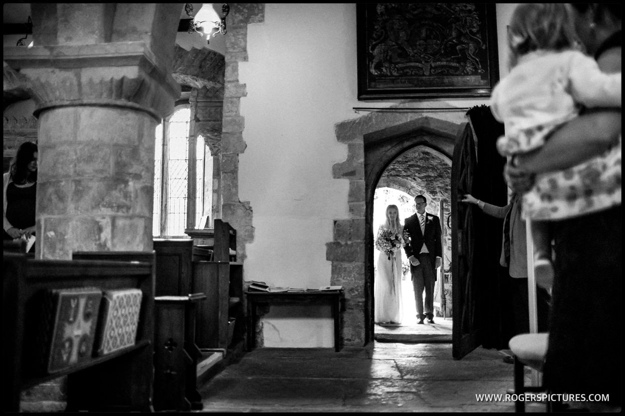 Father and daughter enter church for wedding