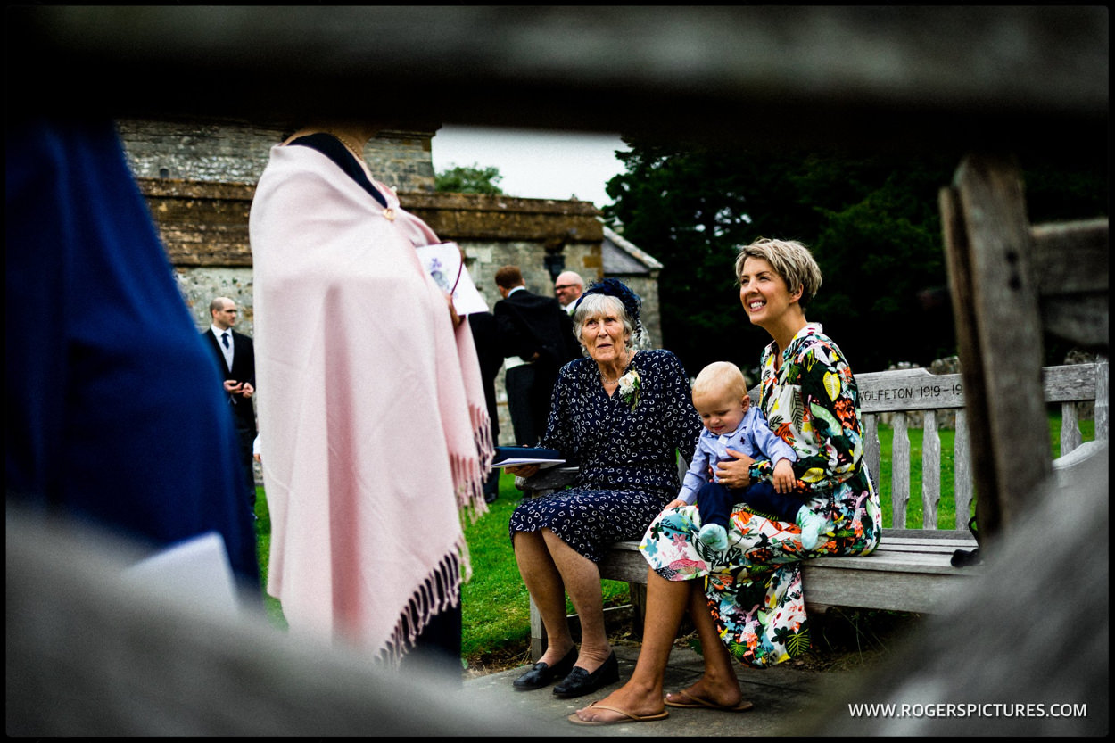 Guests sit on a bench outside Dorset wedding