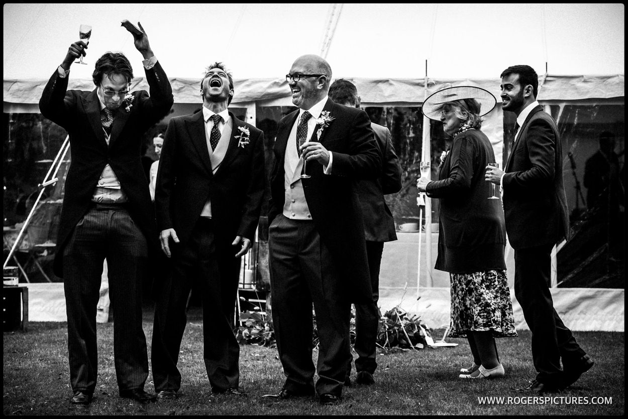 Black-and-white photograph of guests laughing at a wedding
