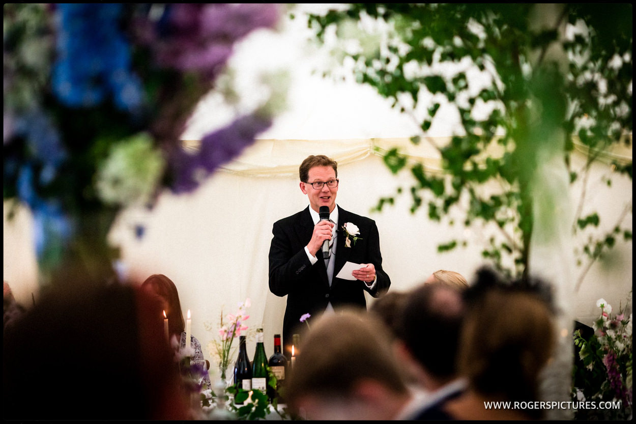 Father of the bride speaks in a marquee