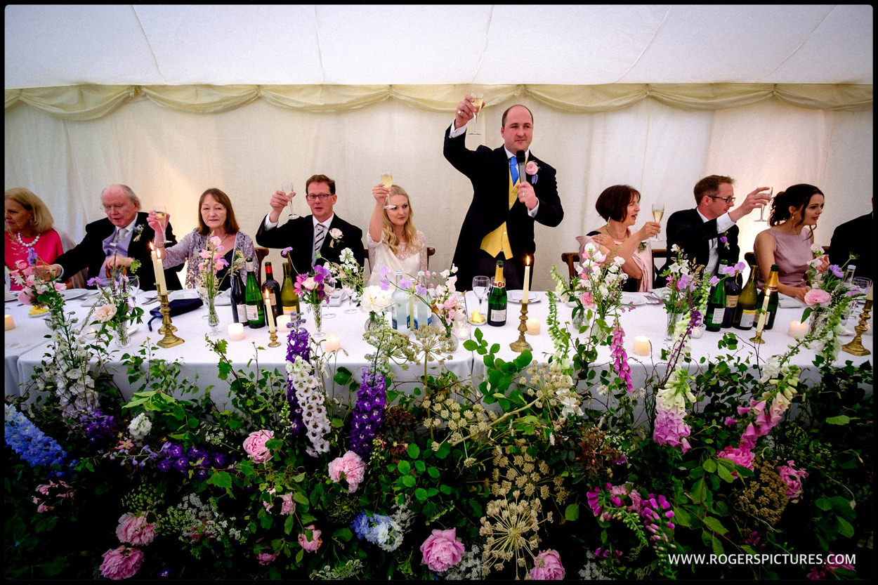 Groom toasts guests at a marquee wedding