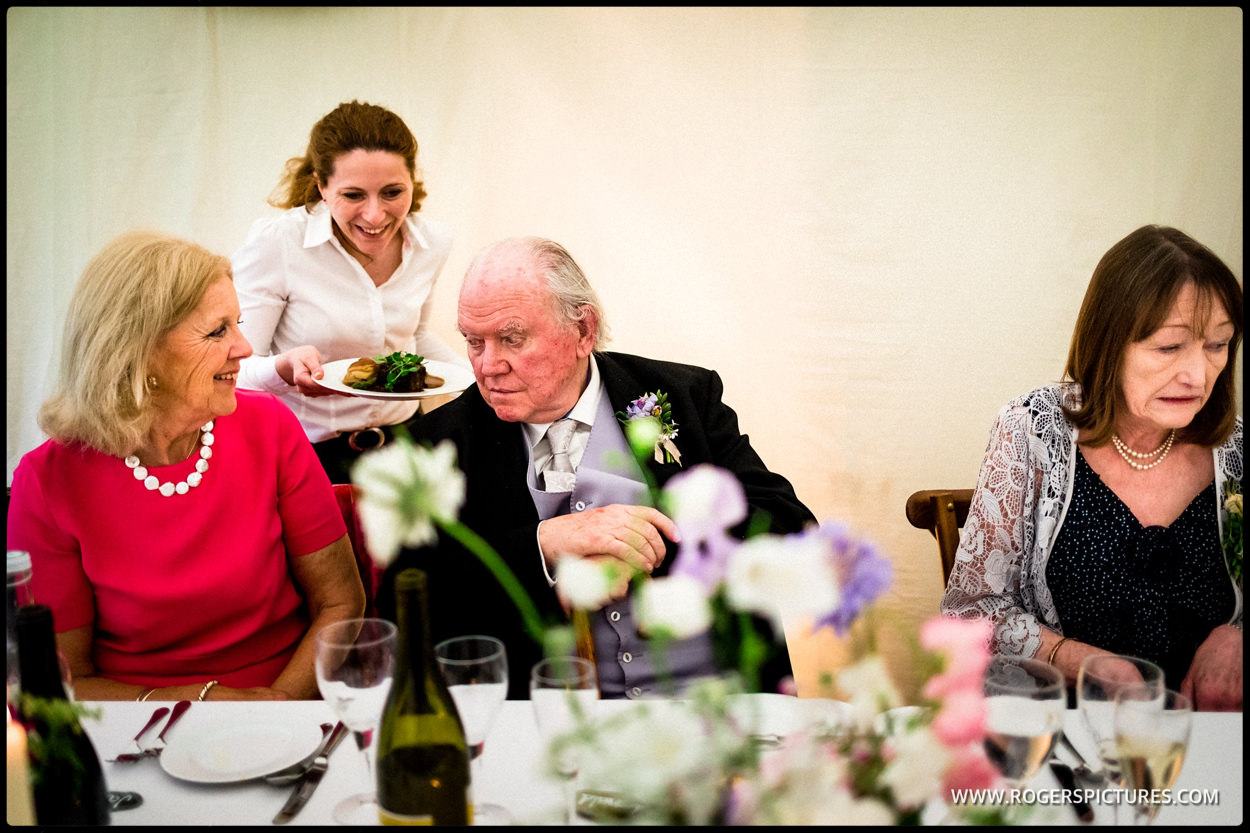 Grandparents being served wedding breakfast