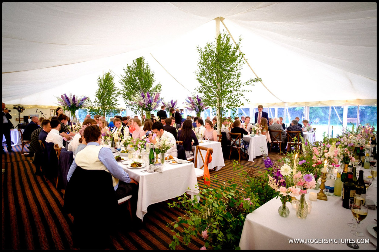 Trees and flowers inside marquee at a wedding