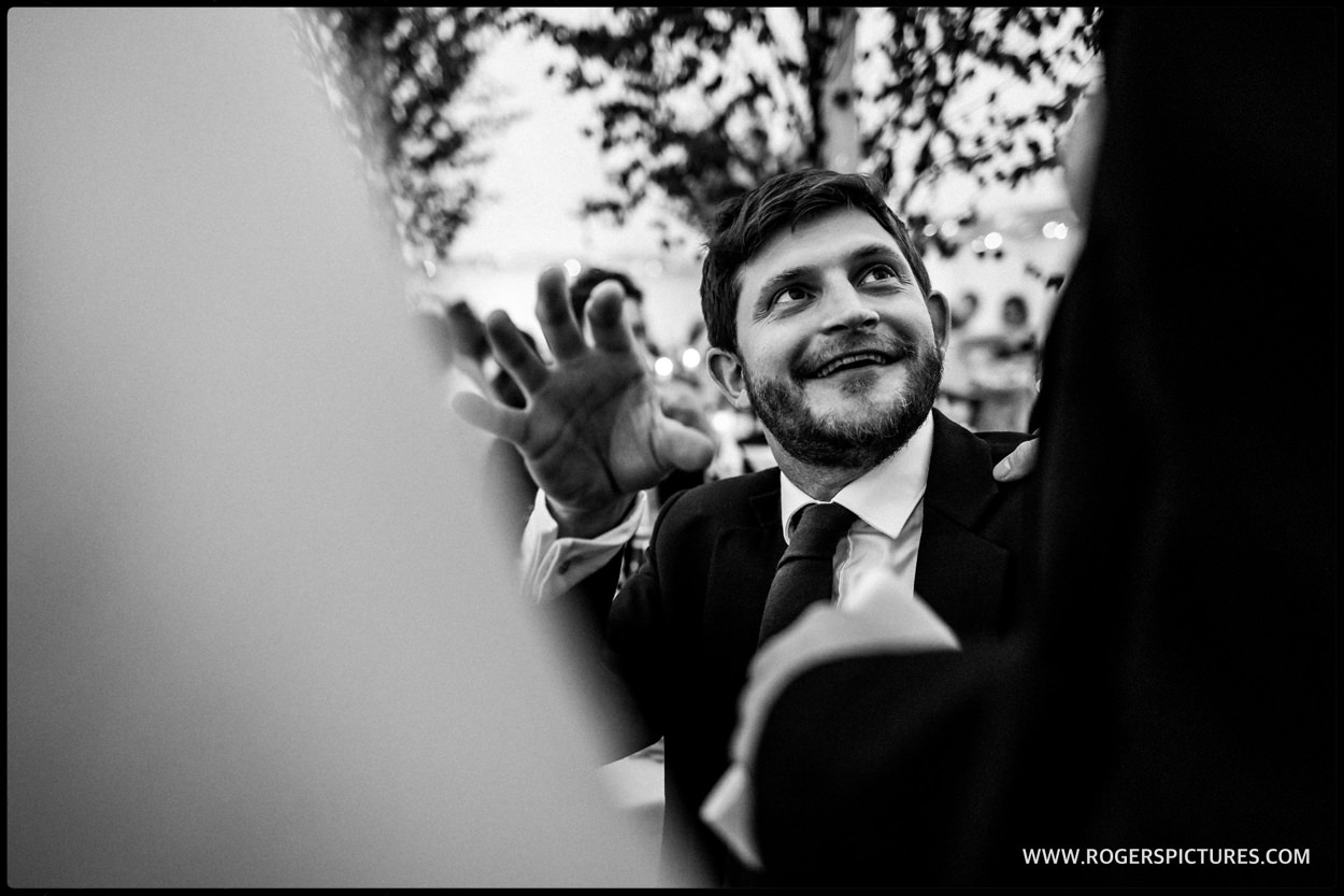 Black-and-white reportage of wedding guest in marquee