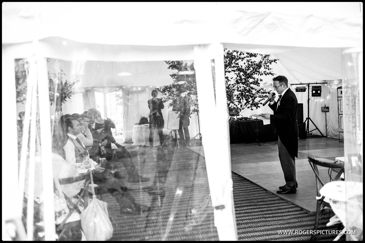 Best man giving a speech from a marquee