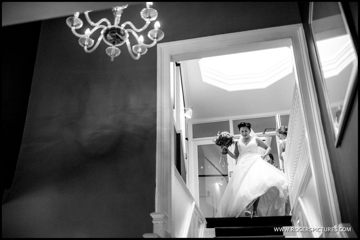 Bride waking down stairs at Banyers House Hotel in Royston