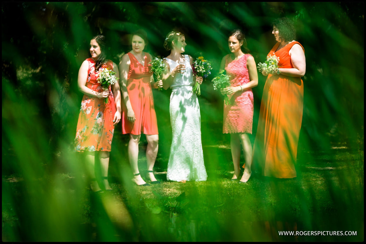 Bride and bridesmaids by the lake at Minstrel Court wedding