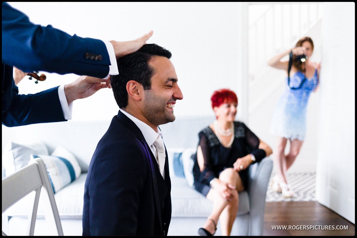 Groom being prepared by his best man at the Stolisma at a Greek Cypriot wedding