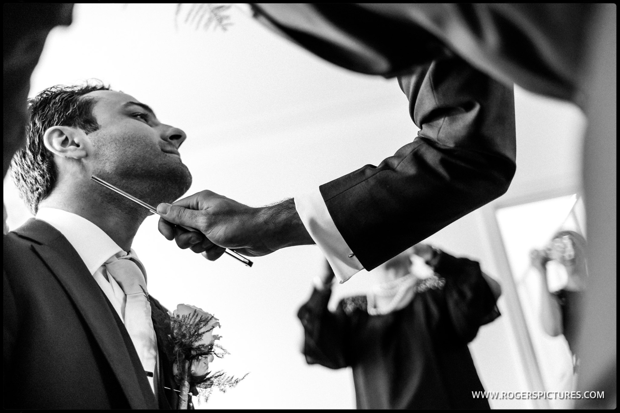 Best man shaving a groom at the Stolisma at a Greek Cypriot wedding
