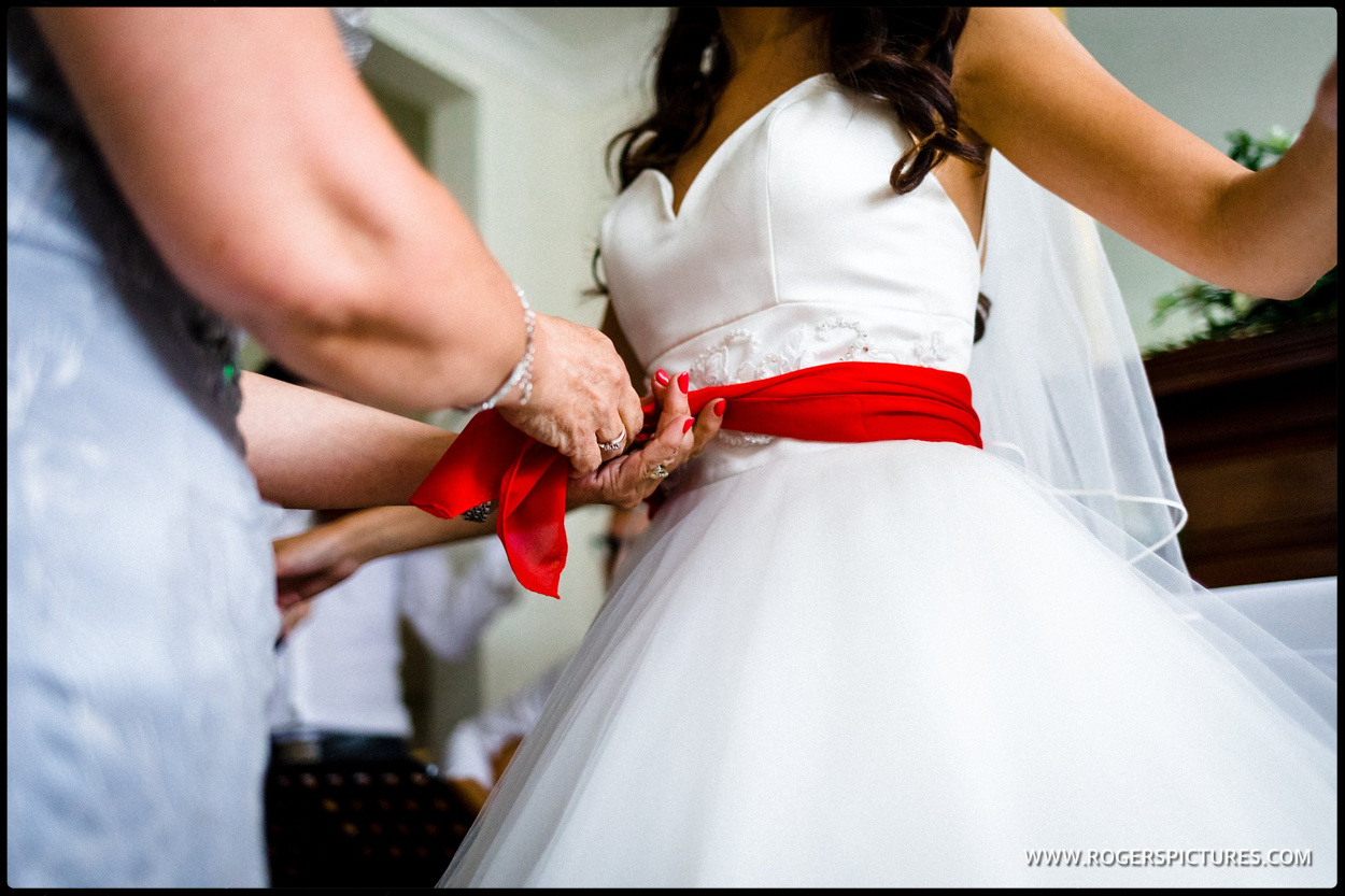Red scarf passed round brides waist at the Stolisma at a Greek Cypriot wedding