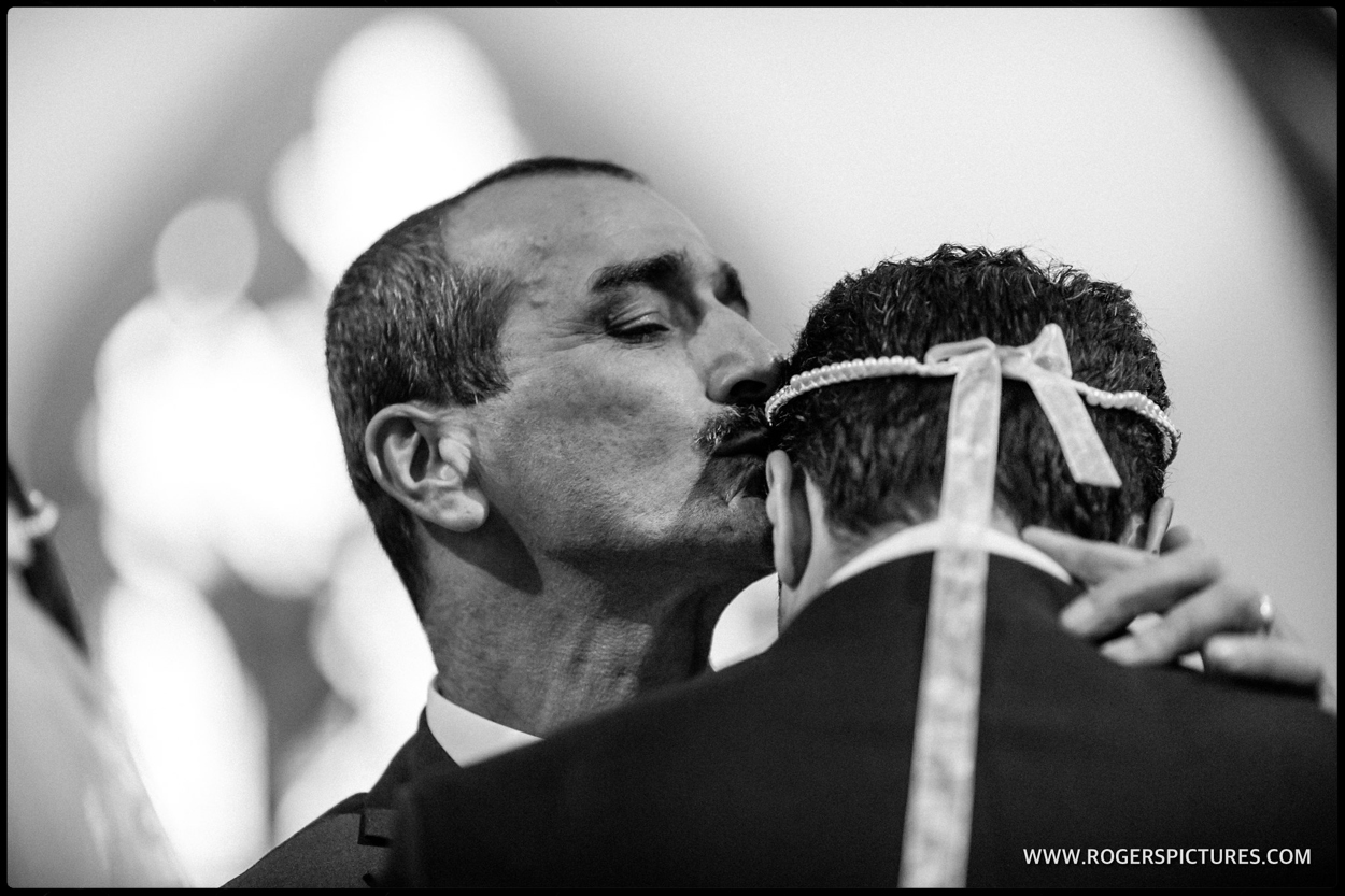 Father kisses his son at a Greek wedding