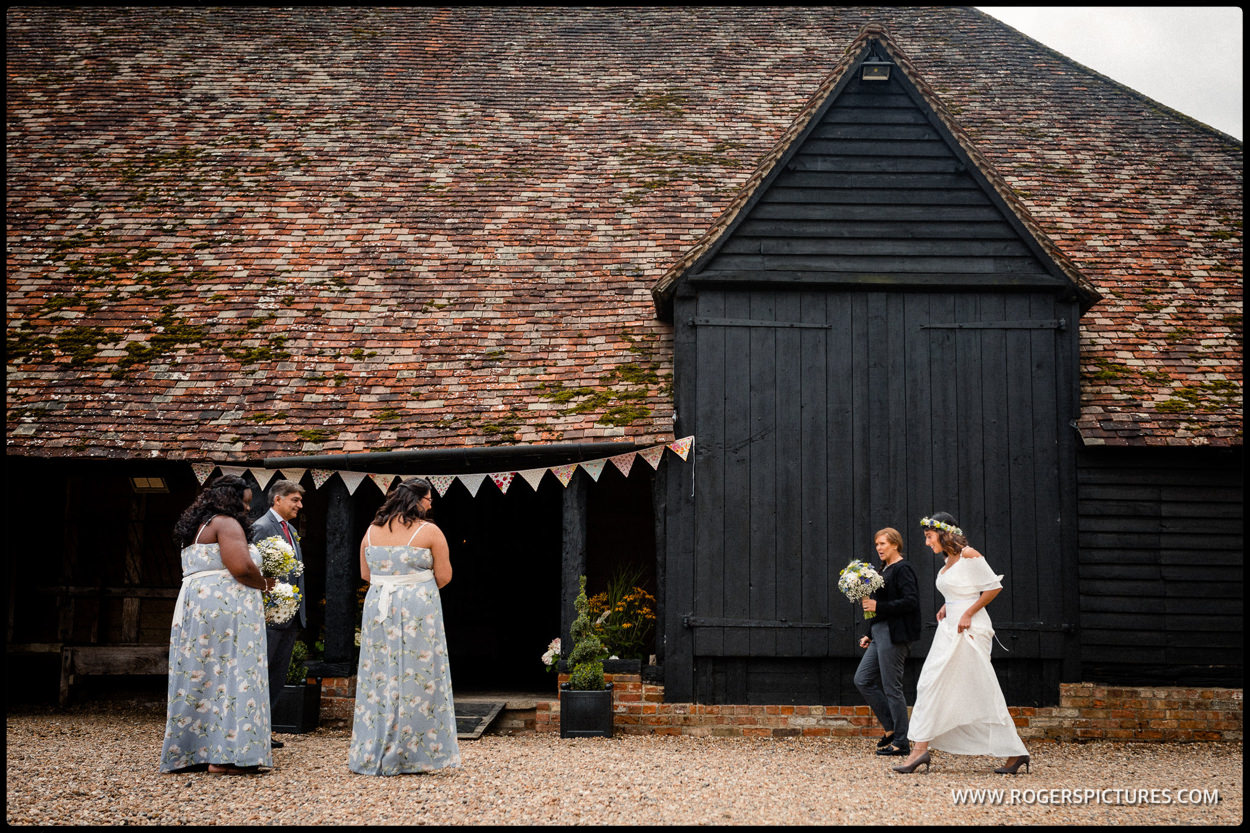 Bride walks past wooden doors before a barn wedding in Hertfordshire