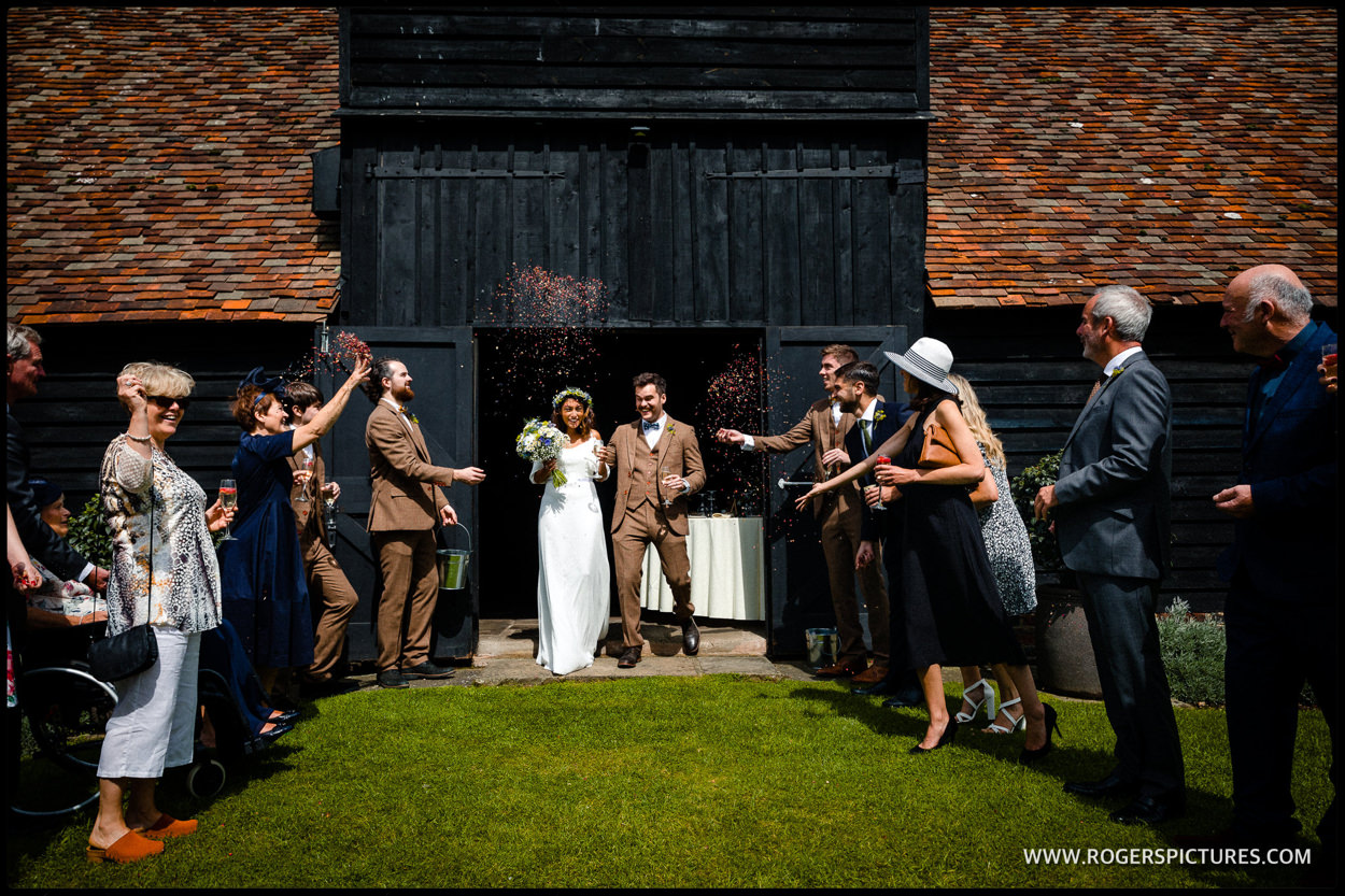 Confetti being thrown at a wedding at Priory Barn in Little Wymondley, Hertfordshire