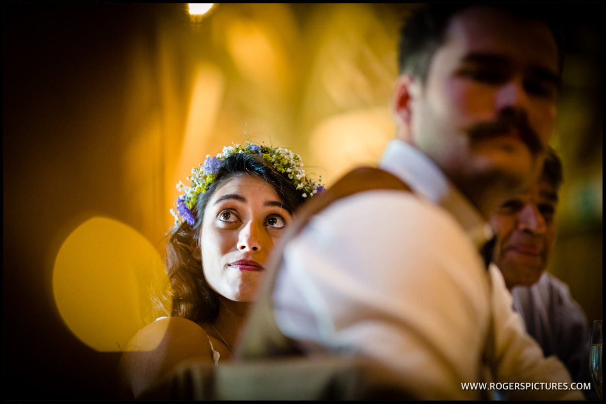 Bride listens to speeches in the barn during a wedding reception