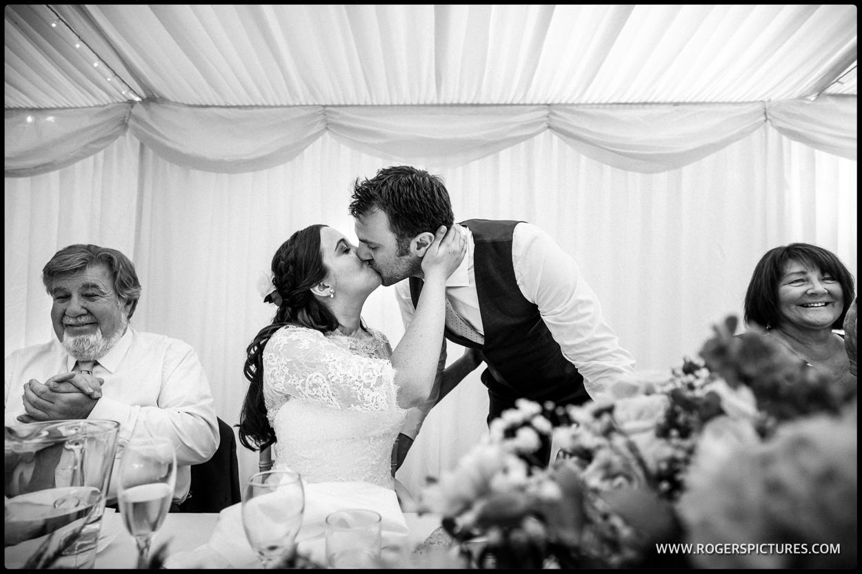Bride and groom kiss after speeches in th emarquee