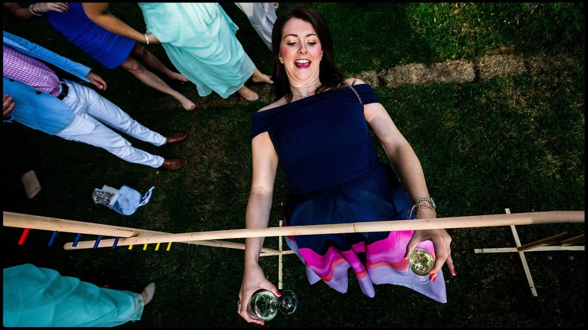 Aerial view of a wedding guest holding glasses of wine while doing the limbo