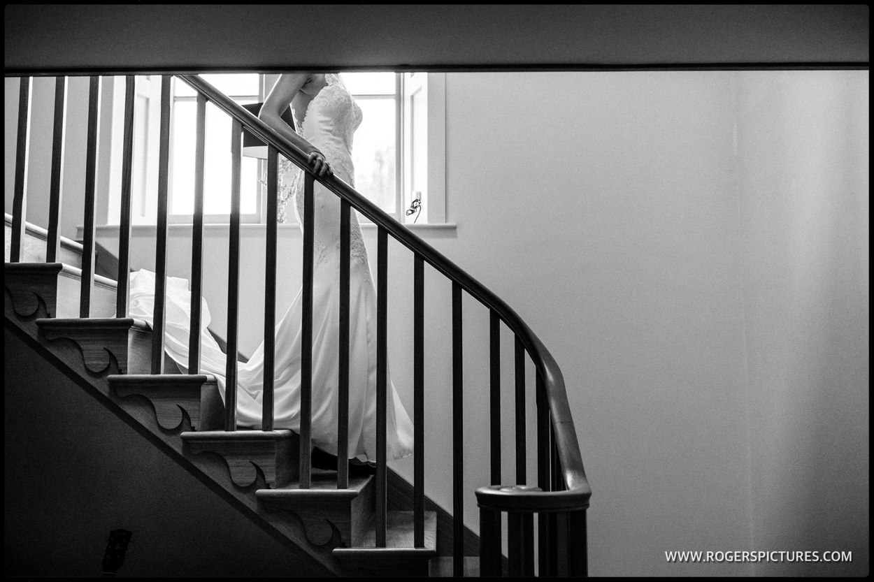 Bride in wedding dress walks down stairs