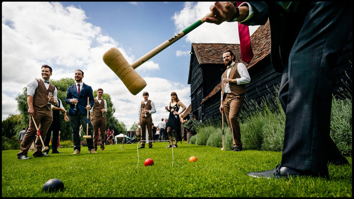Low angle photograph of wedding guests playing croquet on a grass lawn