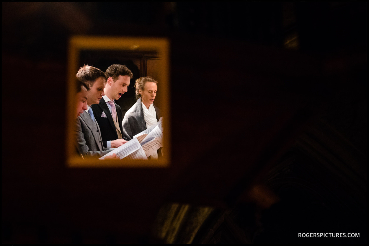 Wedding guests singing at at St Etheldreda's Church in London