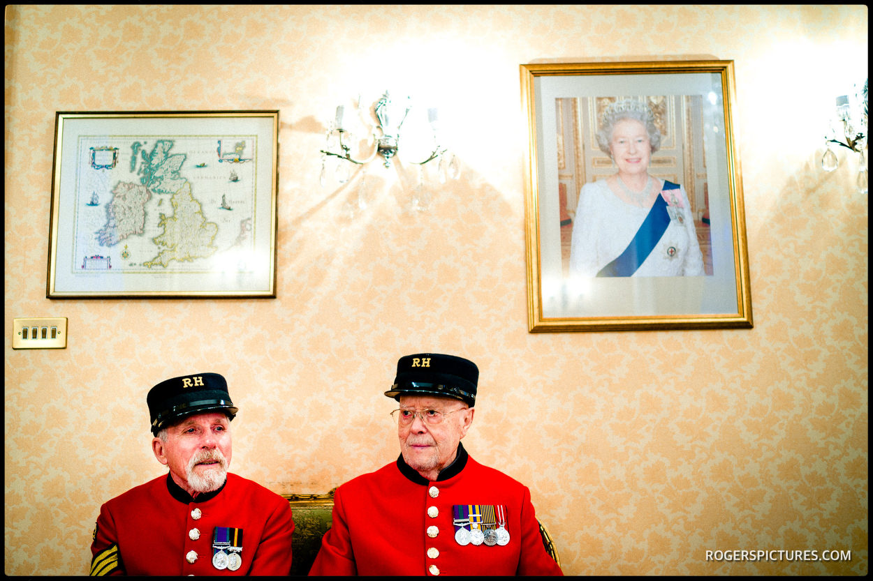 Chelsea Pensioners below a portrait of Queen Elizabeth II at the Town Hall