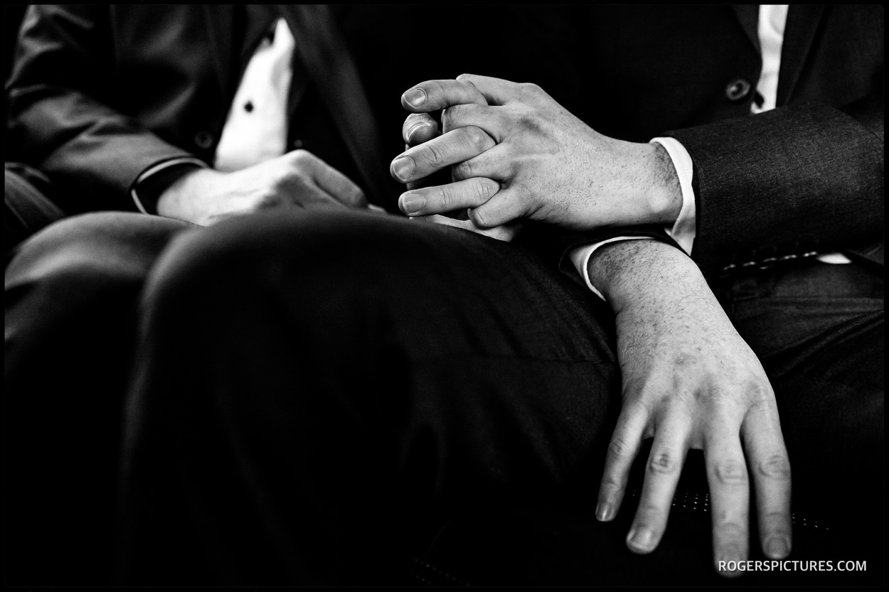 Documentary wedding picture of grooms holding hands