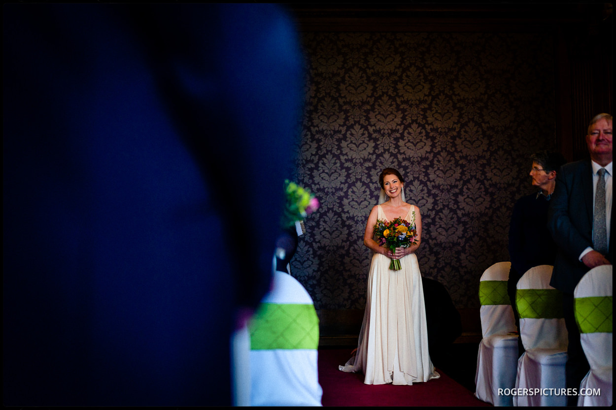 Bride enters ceremony at Nutfield Priory Hotel in Surrey