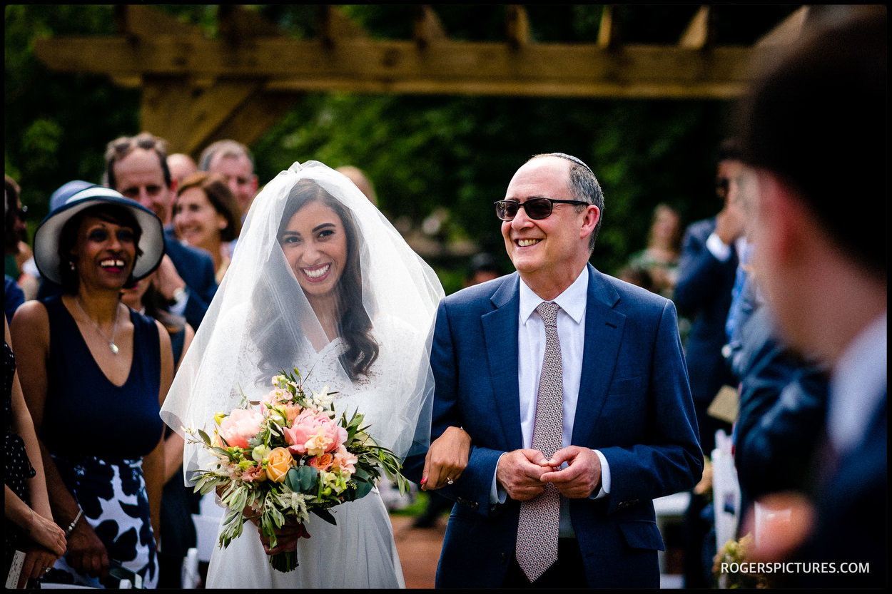 Bride and father of the bride walk down the aisle towards the Chuppah